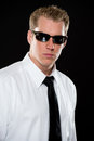 Young man in sunglasses portrait of a male model wearing a white shirt black necktie and dark shot on a black background using Royalty Free Stock Photography