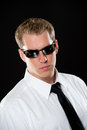 Young man in sunglasses portrait of a male model wearing a white shirt black necktie and dark shot on a black background using Stock Photos