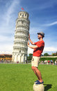 Young man supporting the leaning tower of pisa smiling tourist italy optical illusion great and a little photographed on a Royalty Free Stock Photos