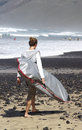Young man with surf a caryying a surfboard on the beach famara lanzarote island Royalty Free Stock Photo