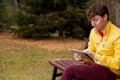 Young man with tablet sits in the park digital on a bench Royalty Free Stock Images