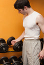 Young man take dumbbells in sport club Royalty Free Stock Photos