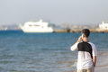 Young man talking on mobile phone at sea attractive holding smartphone using app making call while walking shore to white yacht Royalty Free Stock Image