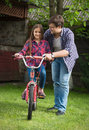Young man teaching girl how to ride a bicycle at park Royalty Free Stock Photo