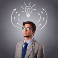 Young man thinking with arrows and light bulb overhead standing Stock Photos