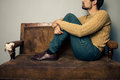 Young man thinking on the couch is sitting an old worn out sofa and Stock Photography