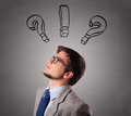 Young man thinking with question marks overhead standing and Stock Images