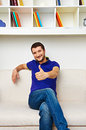 Young man with thumbs up handsome sitting on the sofa and smiling Royalty Free Stock Photography