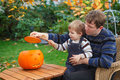 Young man and toddler boy making halloween pumpkin men little having fun with face Stock Image