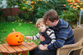 Young man and toddler boy making halloween pumpkin men little having fun with face Royalty Free Stock Images