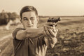 Young man took aim with pistol near village roads Royalty Free Stock Image