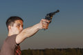Young man took aim with pistol near village roads Stock Image