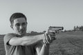 Young man took aim with pistol near village roads Stock Photo