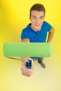 Young man top view holding paint roller. Royalty Free Stock Photo