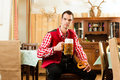 Young man in traditional bavarian tracht in restaurant or pub with beer and steins and pretzel Stock Photos
