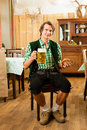 Young man in traditional bavarian tracht in restaurant or pub with beer and steins and pretzel Royalty Free Stock Photography
