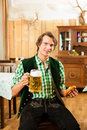 Young man in traditional bavarian tracht in restaurant or pub with beer and steins and pretzel Stock Photography