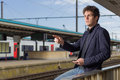 Young man in a train station pointing away and holding smartphone Royalty Free Stock Photos