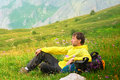 Young man traveller with backpack sitting on grass flowers relaxing mountains background Stock Photo