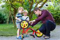Young man and two little sons repairing bicycle outdoors men Royalty Free Stock Photos
