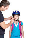 Young man tying helmet on his daughter head Stock Photo