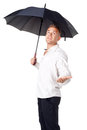 Young man under an umbrella with his hand out isolated on white background Stock Images