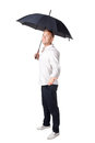 Young man under an umbrella with his hand out isolated on white background Stock Photo