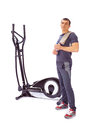 Young man uses elliptical cross trainer Royalty Free Stock Image
