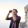 Young man using binoculars outdoors for birdwatching Royalty Free Stock Photo