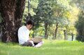 Young man using his laptop on the grass Stock Photos
