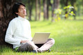 Young man using his laptop on the grass Royalty Free Stock Photos