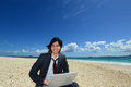 Young man using laptop on the beach picture of a a beautiful sea in okinawa Royalty Free Stock Photography