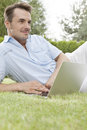 Young man using laptop while looking away in park Royalty Free Stock Images