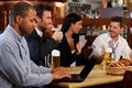 Young man using laptop at pub men browsing internet in looking screen friends drinking beer background Royalty Free Stock Image