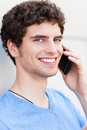 Young man using mobile phone standing outdoors with Royalty Free Stock Photos