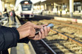 Young man using a smartphone in a train station Royalty Free Stock Photo