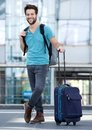 Young man waiting at airport with suitcase and bag Royalty Free Stock Photo