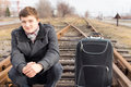 Young man waiting at a rural siding for a train Royalty Free Stock Photo