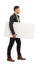 Young man walking with the blank banner handsome under his arm full length studio shot isolated on white Stock Images