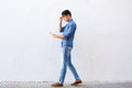 Young man walking and reading text message on cell phone Royalty Free Stock Photo