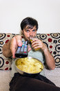 Young man watching television, eating potato chips and drinking Royalty Free Stock Photo