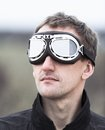Young man wearing aviator goggles motorcycle glasses at the airfield Royalty Free Stock Photos
