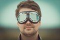 Young man wearing aviator goggles motorcycle glasses at the airfield Royalty Free Stock Image