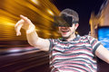 Young man is wearing 3D virtual reality headset and is playing video games. Royalty Free Stock Photo