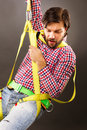 Young man wearing a fall protection harness and lanyard for wor work at heights looking down gray background Royalty Free Stock Photos