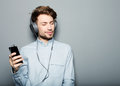 Young man wearing headphones and holding mobile phone Royalty Free Stock Photo
