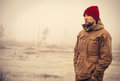 Young man wearing winter hat clothing outdoor with foggy nature on background travel lifestyle and melancholy emotions concept Royalty Free Stock Photo