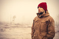 Young man wearing winter hat clothing outdoor with foggy nature on background travel lifestyle and melancholy emotions concept Royalty Free Stock Photography