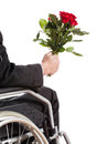 Young man on wheelchair waiting for his girlfirend girlfriend with flowers Royalty Free Stock Photography