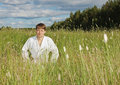 Young man in white kimono sits in grass Stock Photo